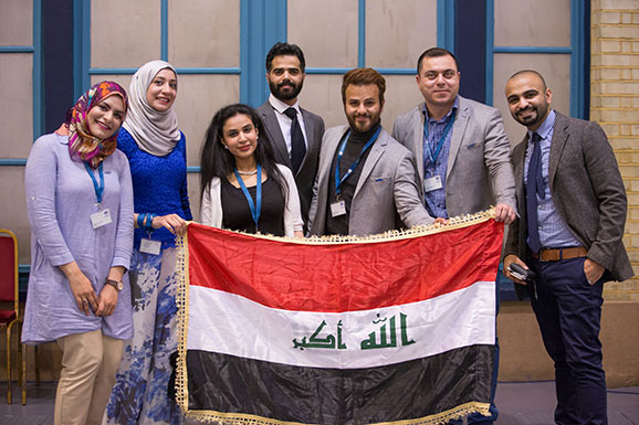 Scholars with flag of Iraq