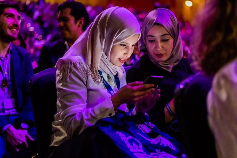 Scholar on phone during Orientation 2018