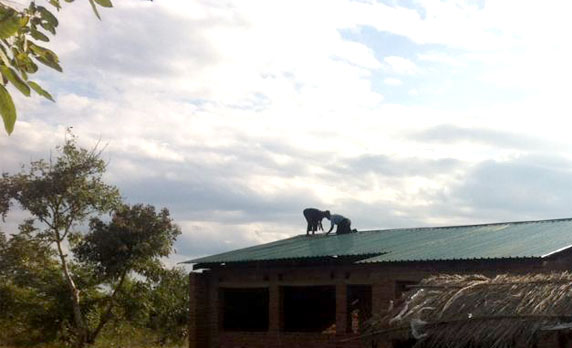 Construction workers install the roof